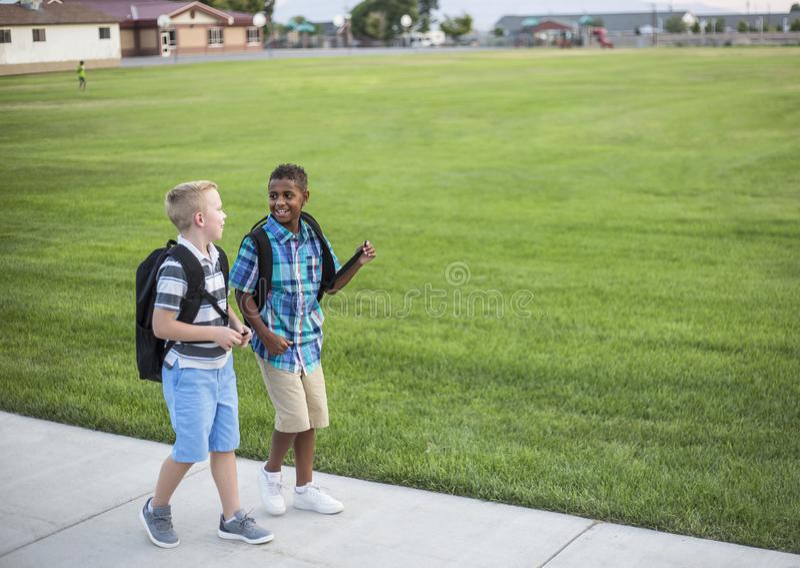 Dos niños diversos de la escuela que caminan a casa junto después de escuela fotografía de archivo