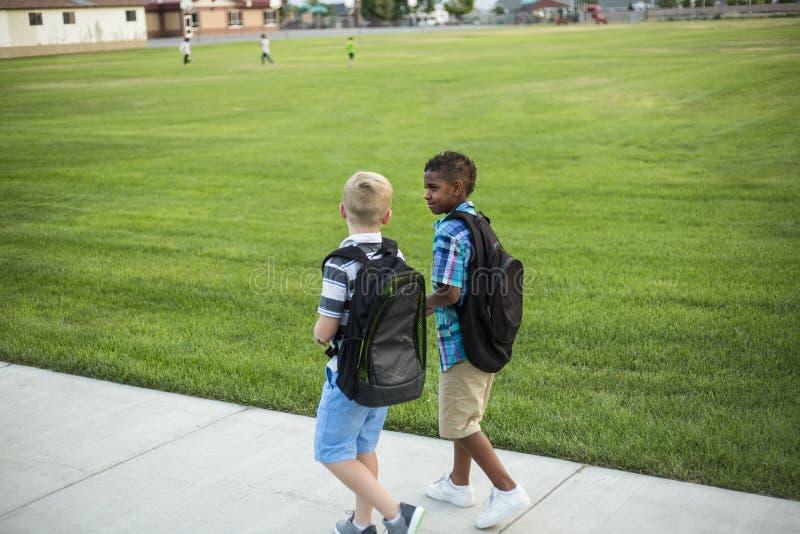 Dos niños diversos de la escuela que caminan y que hablan junto en la manera con la escuela imagen de archivo libre de regalías