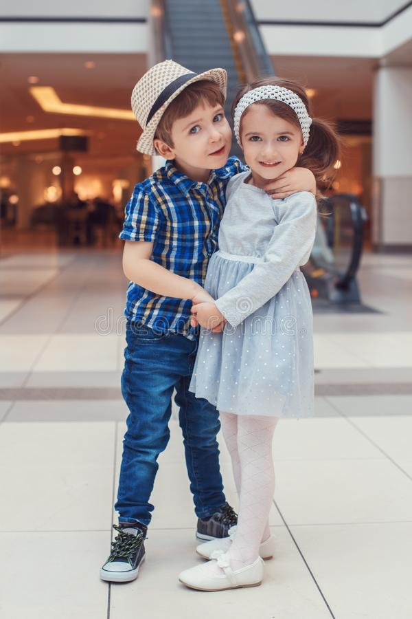 Dos niños divertidos adorables lindos caucásicos blancos muchacho y muchacha que abrazan besarse imagen de archivo