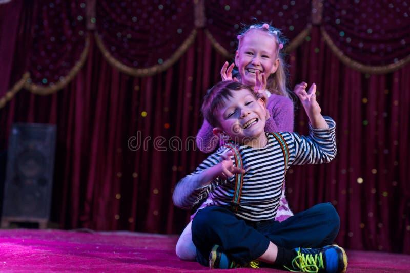 Dos niños divertidos que actúan como monstruos en etapa imagen de archivo