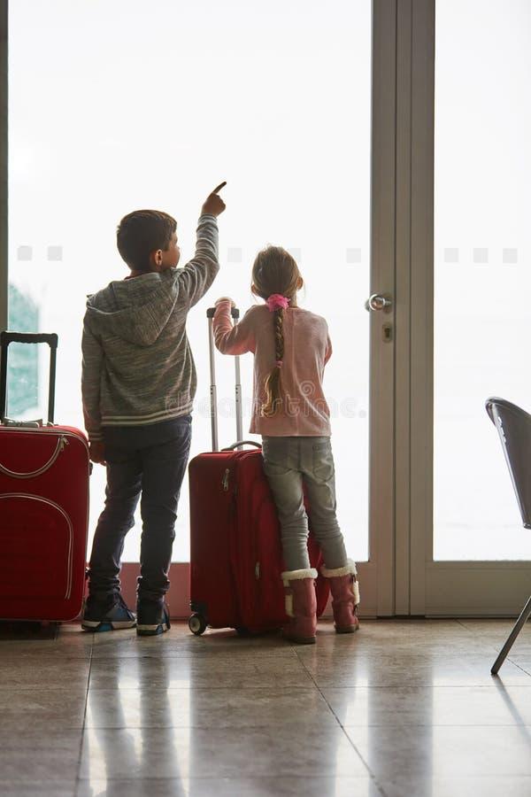 Dos niños en el aeropuerto miran la pista imágenes de archivo libres de regalías