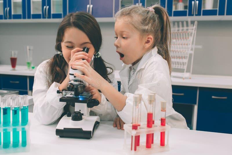 Dos niños en laboratorio cubren el aprendizaje de química en laboratorio de la escuela Científicos jovenes en la fabricación prot imagen de archivo libre de regalías