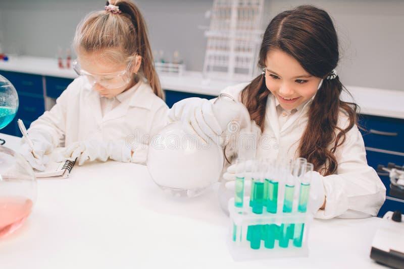 Dos niños en laboratorio cubren el aprendizaje de química en laboratorio de la escuela Científicos jovenes en la fabricación prot imagenes de archivo