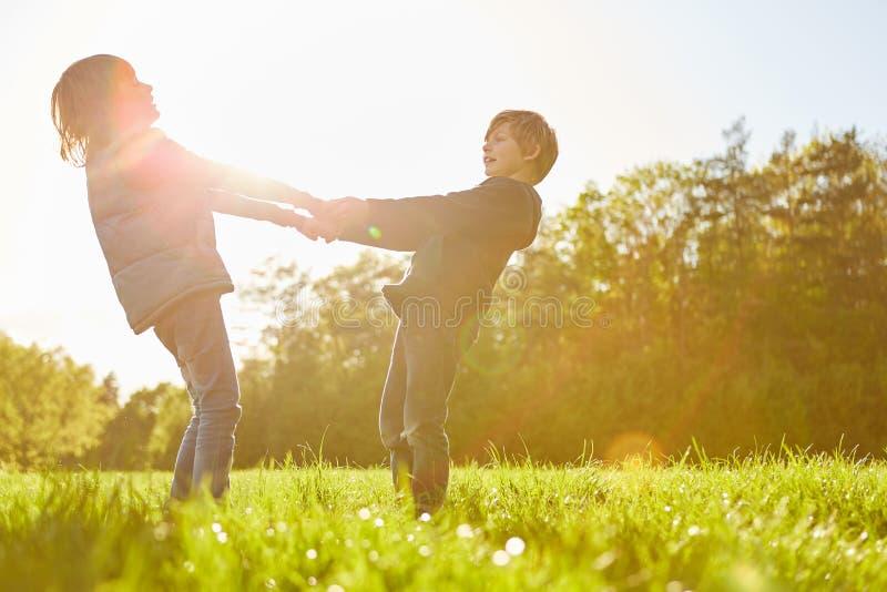 Dos niños están bailando en un prado en la sol foto de archivo
