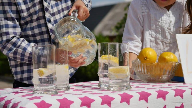 Dos niños están vendiendo la limonada en un puesto de limonadas hecho en casa en un día soleado con una muestra del precio para u fotos de archivo libres de regalías