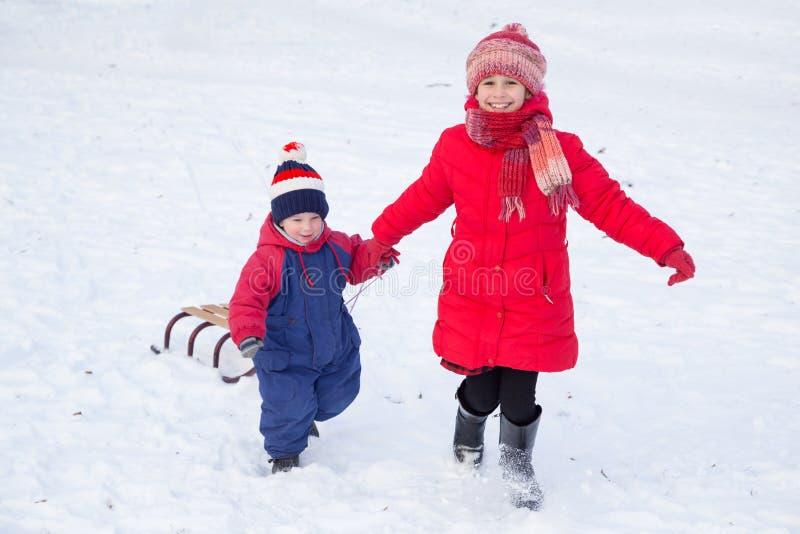 Dos niños felices con el trineo que caminan en nieve foto de archivo libre de regalías