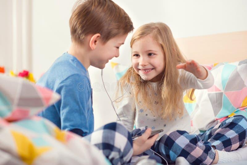 Dos niños felices de los hermanos que tienen la diversión y música que escucha con foto de archivo