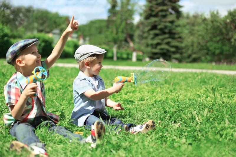 Dos niños felices de los muchachos que se sientan en la hierba que juega y que se divierte junto al aire libre en día de verano fotos de archivo