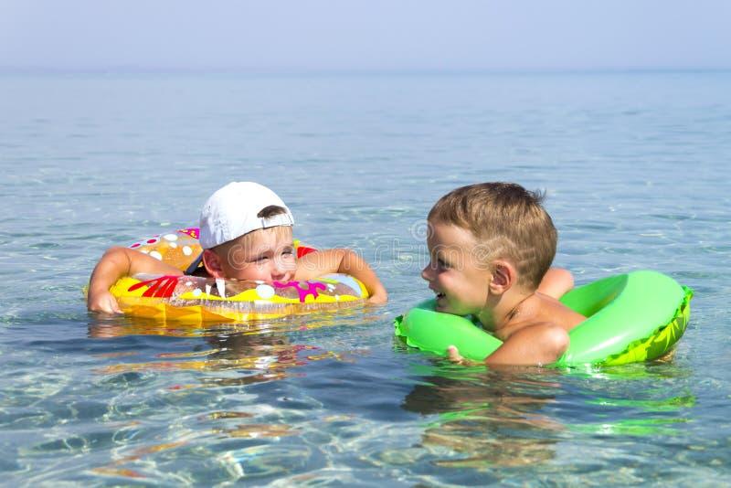 Dos niños felices nadan en los círculos inflables en el mar en el verano imagen de archivo libre de regalías