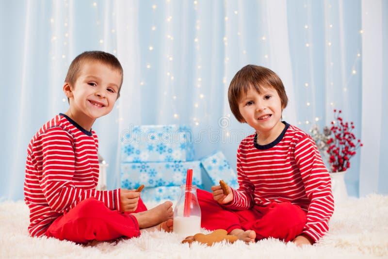 Dos niños felices que comen las galletas en la Navidad y la leche de consumo fotos de archivo