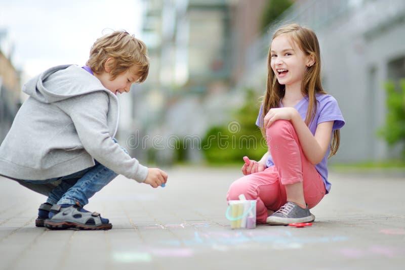 Dos niños felices que dibujan con tizas coloridas en una acera Actividad del verano para los pequeños niños imagenes de archivo