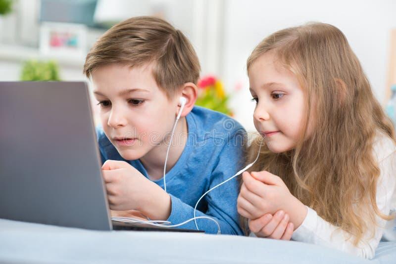 Dos niños felices que juegan con el ordenador portátil y la música que escucha con imágenes de archivo libres de regalías