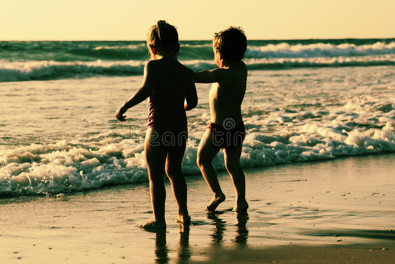 Dos niños felices que juegan en la playa imagenes de archivo