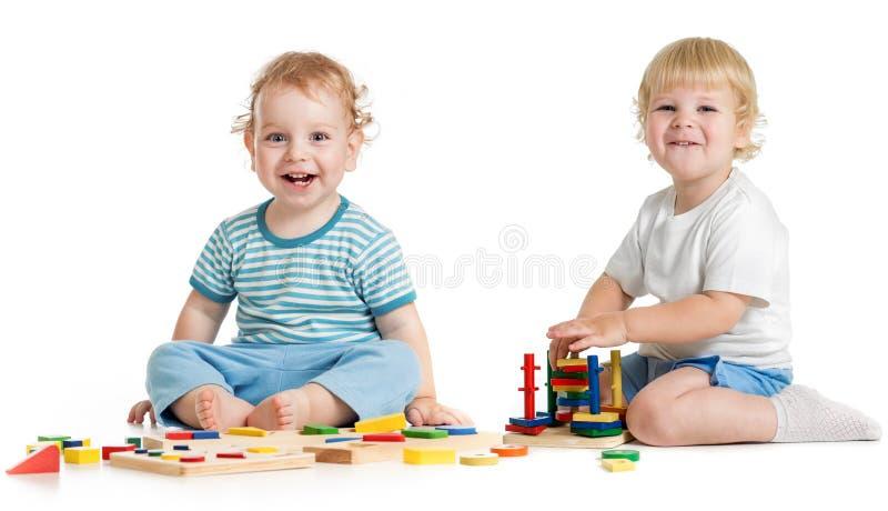 Dos niños felices que juegan los juguetes lógicos imagen de archivo