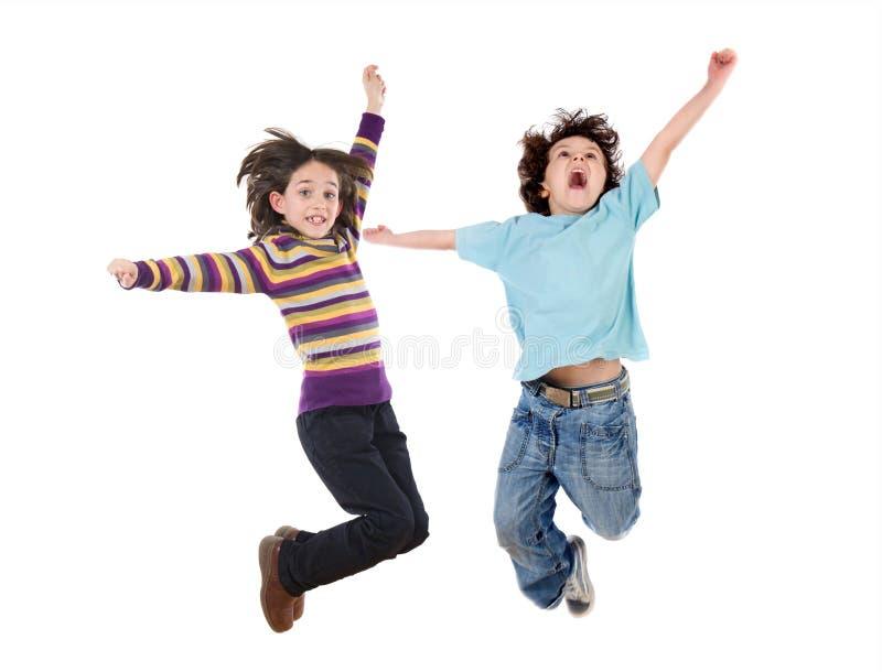 Dos niños felices que saltan inmediatamente imagen de archivo libre de regalías