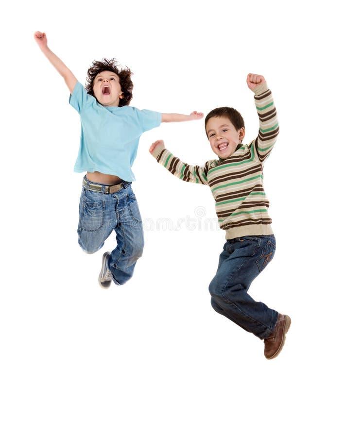 Dos niños felices que saltan inmediatamente imagenes de archivo