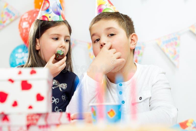 Dos niños felices que se divierten en la fiesta de cumpleaños imagenes de archivo