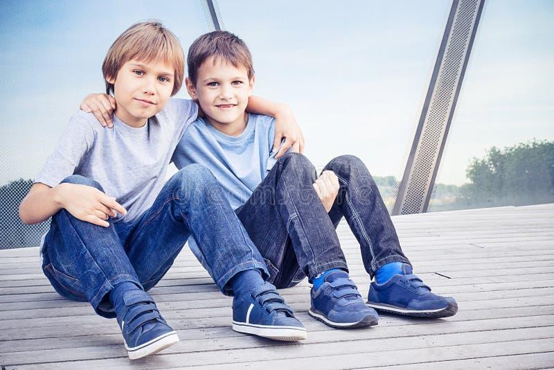 Dos niños felices que se sientan junto y que abrazan imagen de archivo libre de regalías