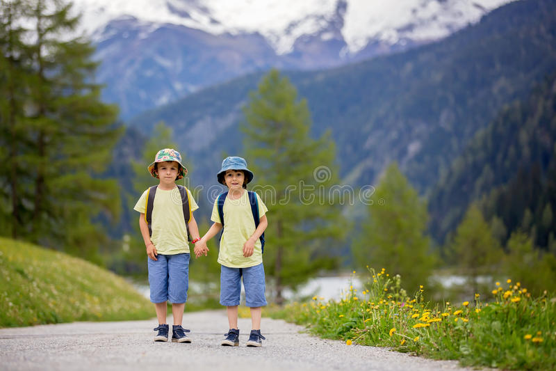 Dos niños, hermanos del muchacho, caminando en una pequeña trayectoria en Al suizo foto de archivo