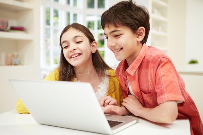Dos niños hispánicos que miran el ordenador portátil foto de archivo
