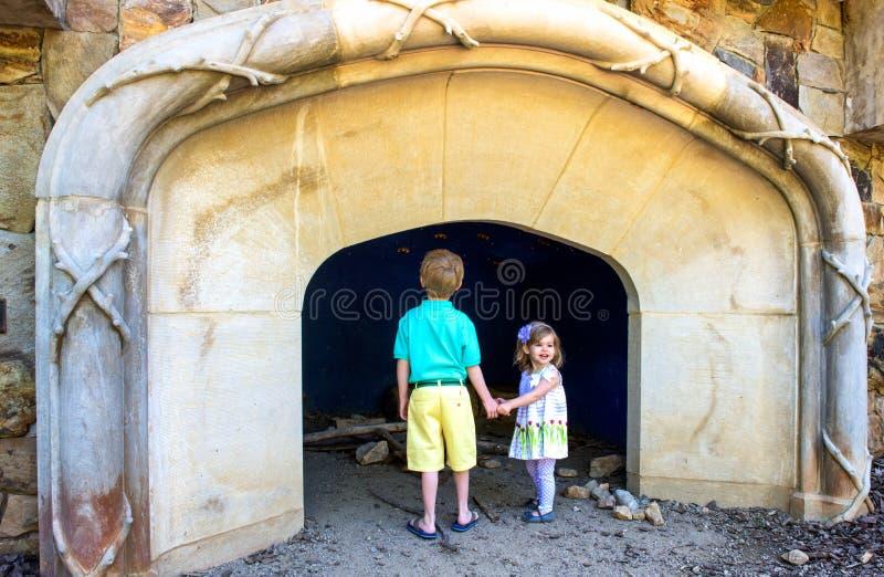 Dos niños jovenes miran una abertura de la cueva en un jardín público imagenes de archivo