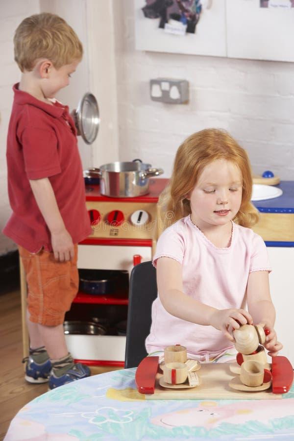 Dos niños jovenes que juegan junto en Montessori/ fotos de archivo