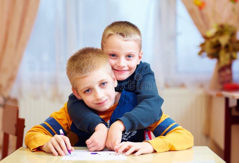 Dos niños lindos, amigos en la escuela de la rehabilitación para los niños con necesidades especiales fotografía de archivo