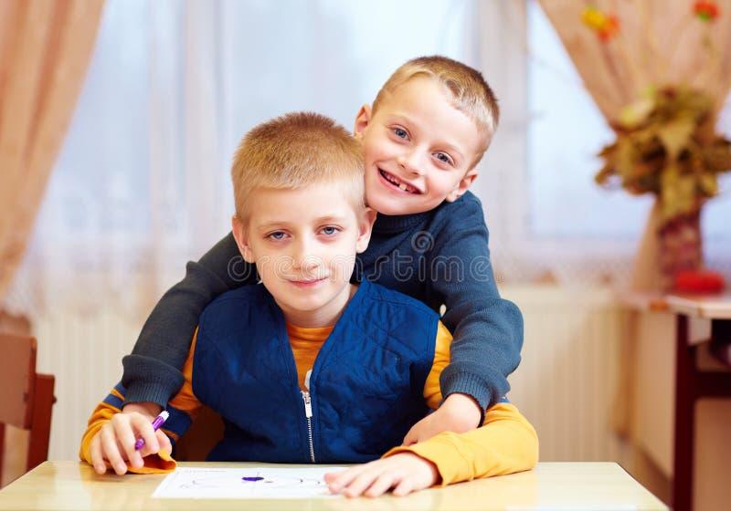 Dos niños lindos, amigos en la escuela de la rehabilitación para los niños con necesidades especiales imagen de archivo libre de regalías