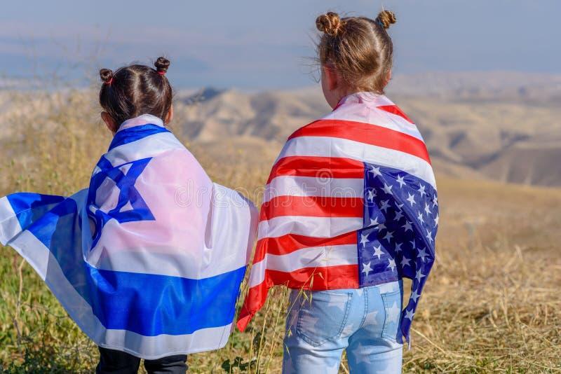 Dos niños lindos con las banderas del americano y de Israel foto de archivo libre de regalías