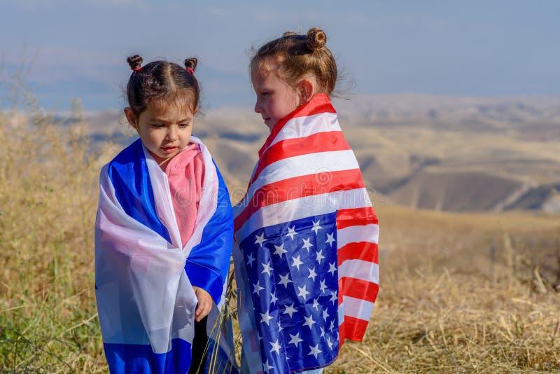 Dos niños lindos con las banderas del americano y de Israel fotos de archivo