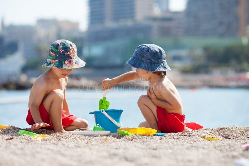 Dos Niños Lindos, Jugando En La Arena En La Playa Imagen