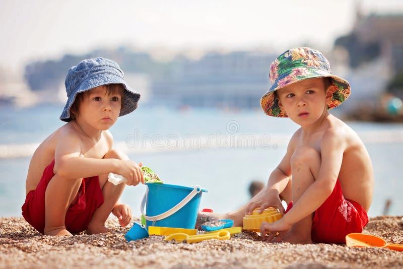 Dos niños lindos, jugando en la arena en la playa fotografía de archivo