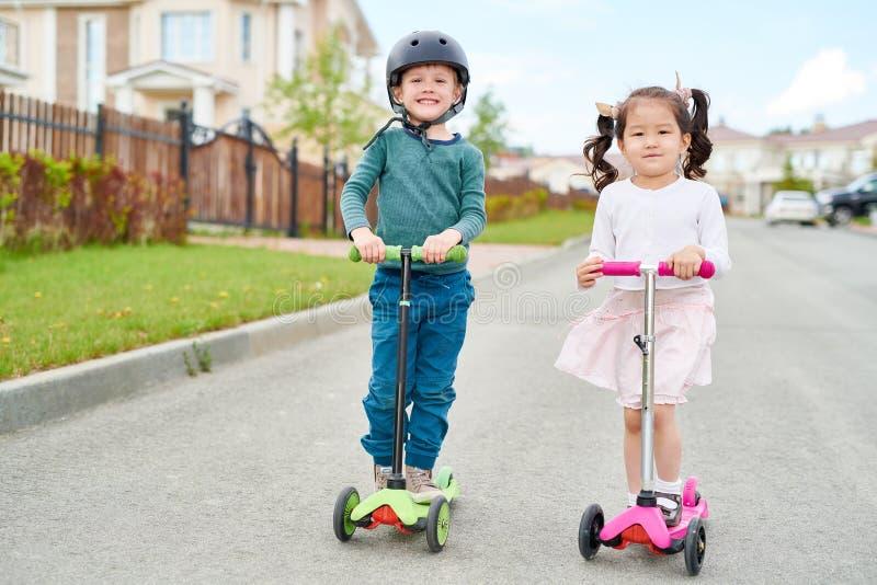 Dos niños lindos que montan las vespas imagen de archivo libre de regalías