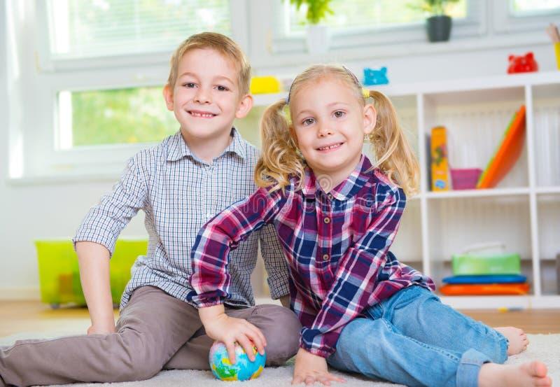 Dos niños listos que exploran el globo foto de archivo libre de regalías