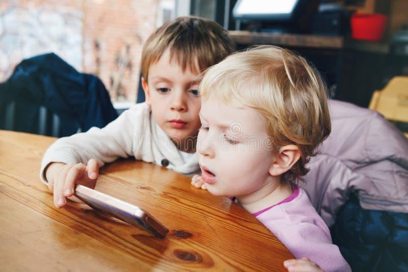 dos niños muchacho y muchacha de los niños que juegan el teléfono celular hacen tabletas juegos imagenes de archivo