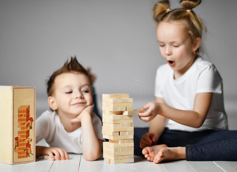 Dos niños muchacho y muchacha en las camisetas blancas están en el piso y juegan Jenga imagen de archivo