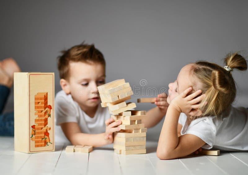 Dos niños muchacho y muchacha en las camisetas blancas mienten en el piso y juegan Jenga fotos de archivo libres de regalías