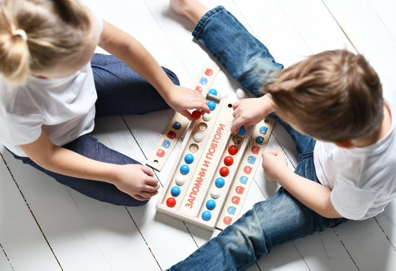 Dos niños muchacho y muchacha en las camisetas y los tejanos blancos juegan al juego educativo para recordar y para repetir imágenes de archivo libres de regalías