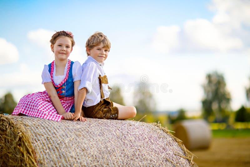Dos niños, muchacho y muchacha en trajes bávaros tradicionales en campo de trigo fotos de archivo libres de regalías