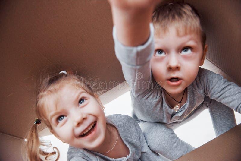 Dos niños muchacho y muchacha que abren una caja de cartón y que suben en el medio de ella Los niños se divierten imagen de archivo