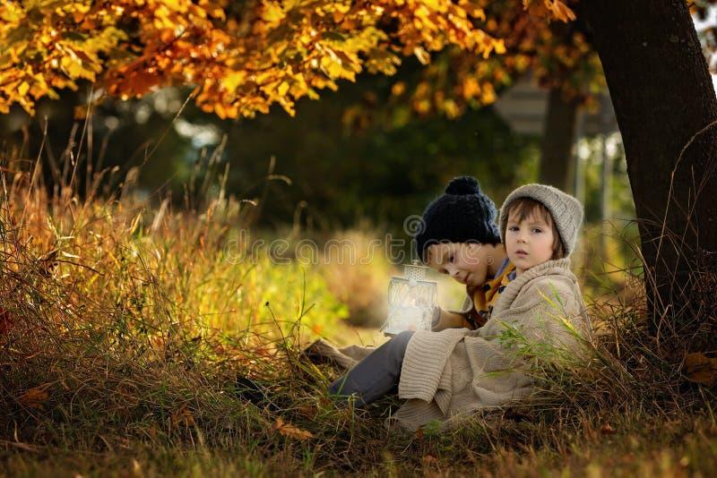Dos niños, muchachos, abrazando debajo de la manta, sentándose debajo de un árbol imagenes de archivo