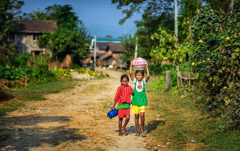Dos niños nepaleses que caminan en su pueblo en Nepal imagenes de archivo