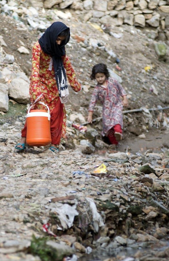 Dos niños paquistaníes que traen el agua foto de archivo