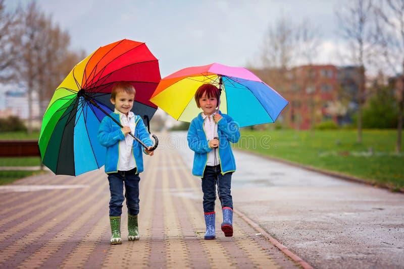 Dos niños pequeños adorables, caminando en un parque en un día lluvioso, juegan imagenes de archivo