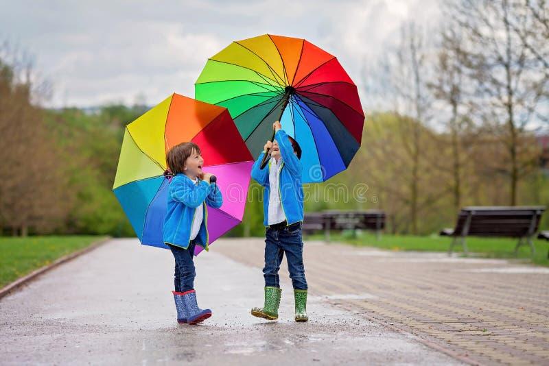 Dos niños pequeños adorables, caminando en un parque en un día lluvioso, juegan fotografía de archivo libre de regalías