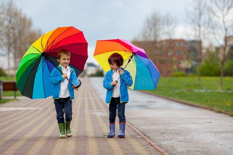 Dos niños pequeños adorables, caminando en un parque en un día lluvioso, juegan imagen de archivo