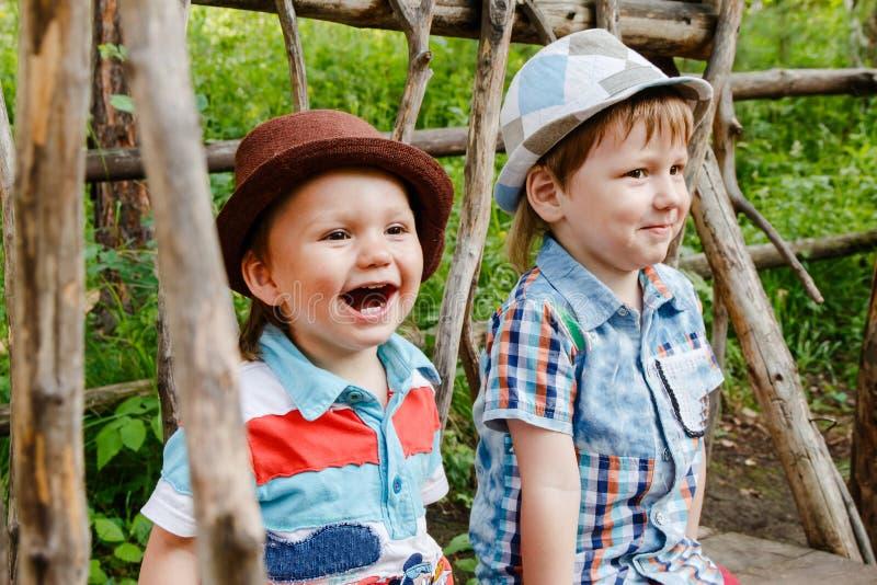 Dos niños pequeños alegres en los sombreros que se sientan en un banco en el parque fotos de archivo