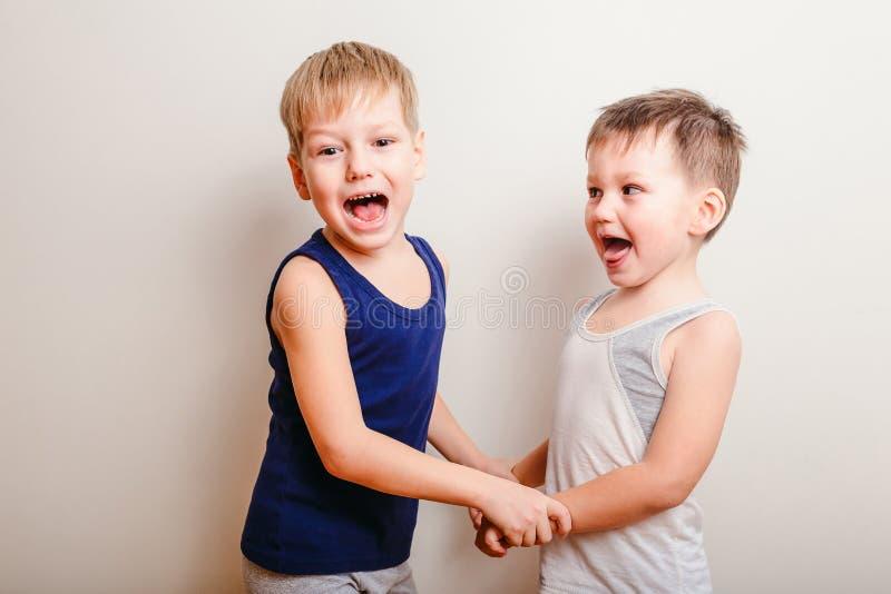 Dos niños pequeños alegres juegan juntos, llevan a cabo las manos y grito fotos de archivo