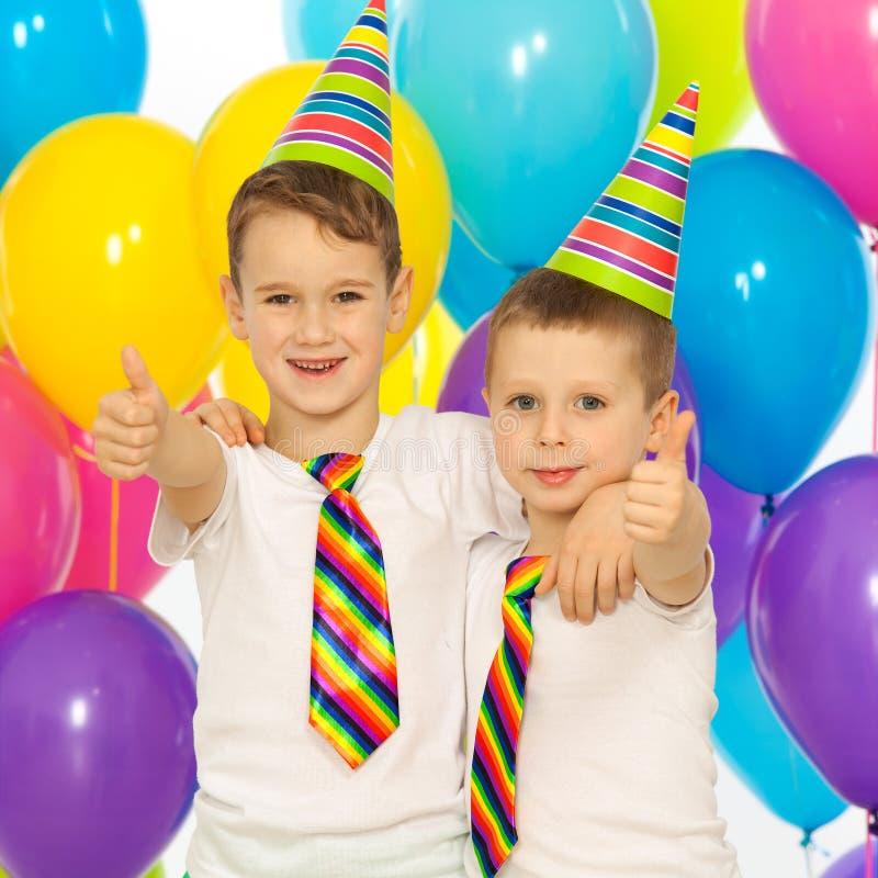 Dos niños pequeños en la fiesta de cumpleaños foto de archivo libre de regalías