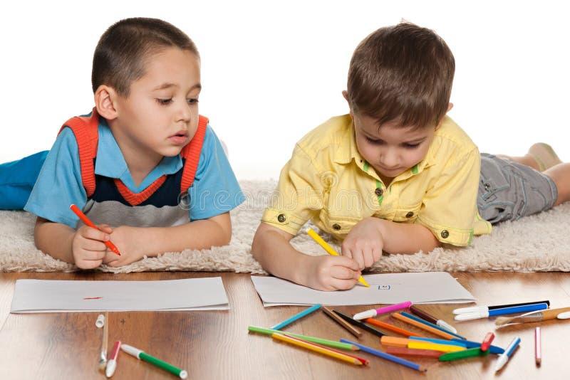 Dos Niños Pequeños Que Dibujan En El Papel Imagen de archivo ...